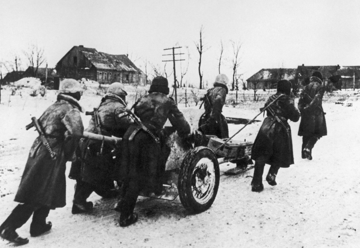 Расчет 45-мм противотанковой пушки по снегу буксирует своё орудие.